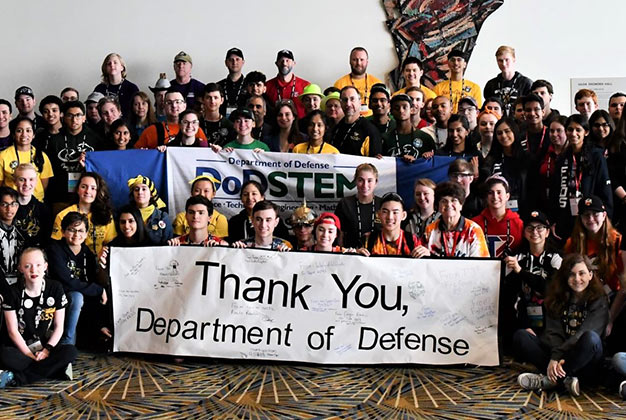 A large group of people holding a sign which says Thank you Department of Defense